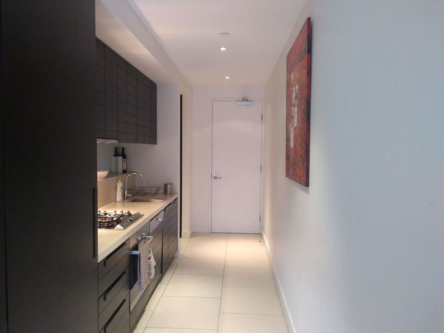 Entrance into modern well equipped galley kitchen