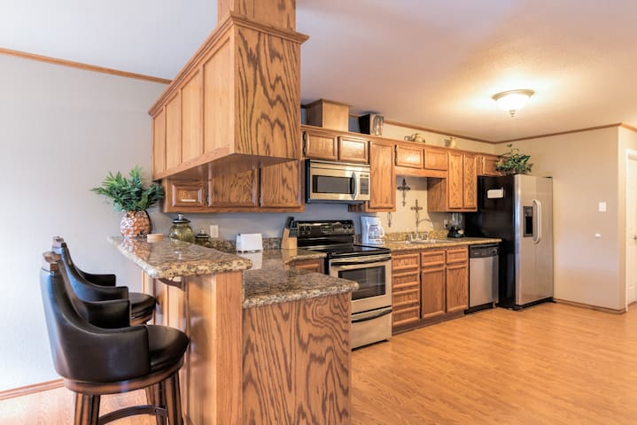 The kitchen has stainless steel appliances and granite counters.
