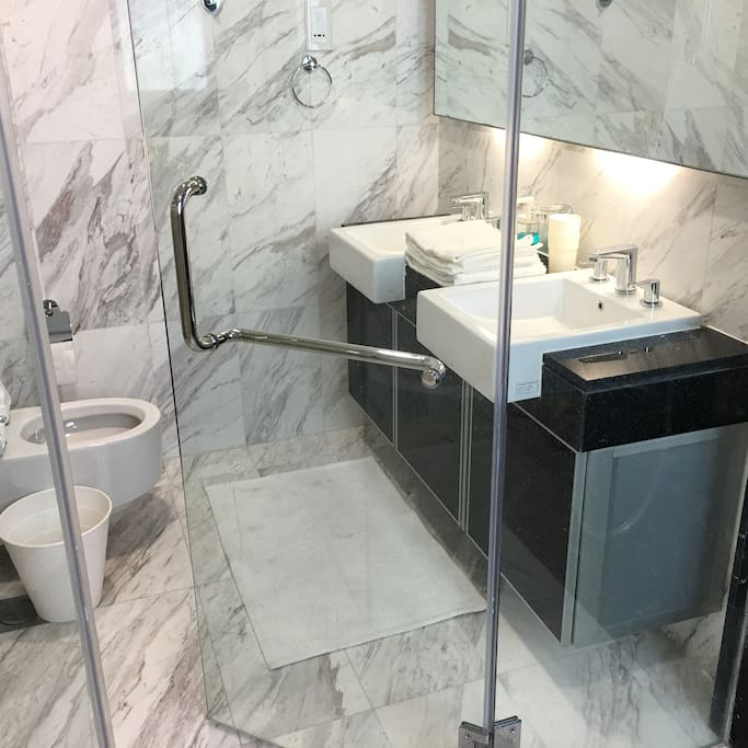 Master bedroom toilet: His and hers sinks located in a marble cocoon