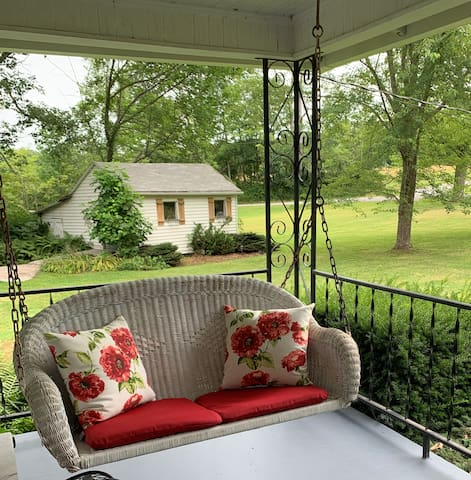 Porch swing with garden cottage in background.