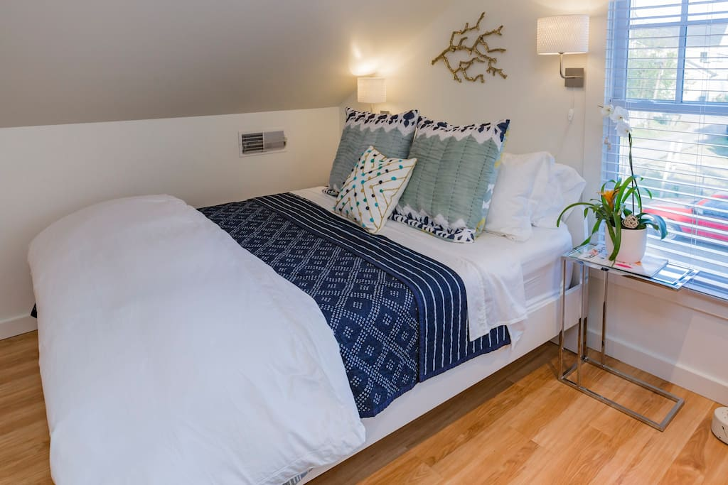 Premium bedding on the comfortable queen sized mattress, with options for down comforter, coverlet, blankets, and an assortment of pillows