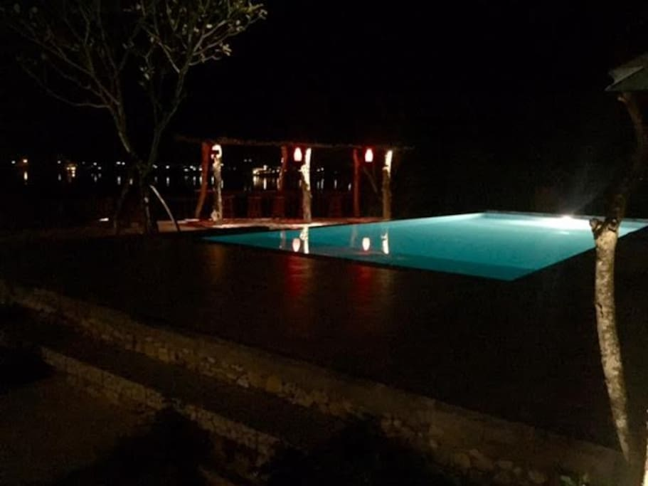 Night time view of the infinity pool and bar area