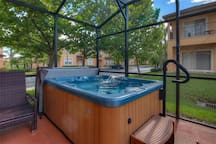 Hot tub spa in screened patio in backyard.