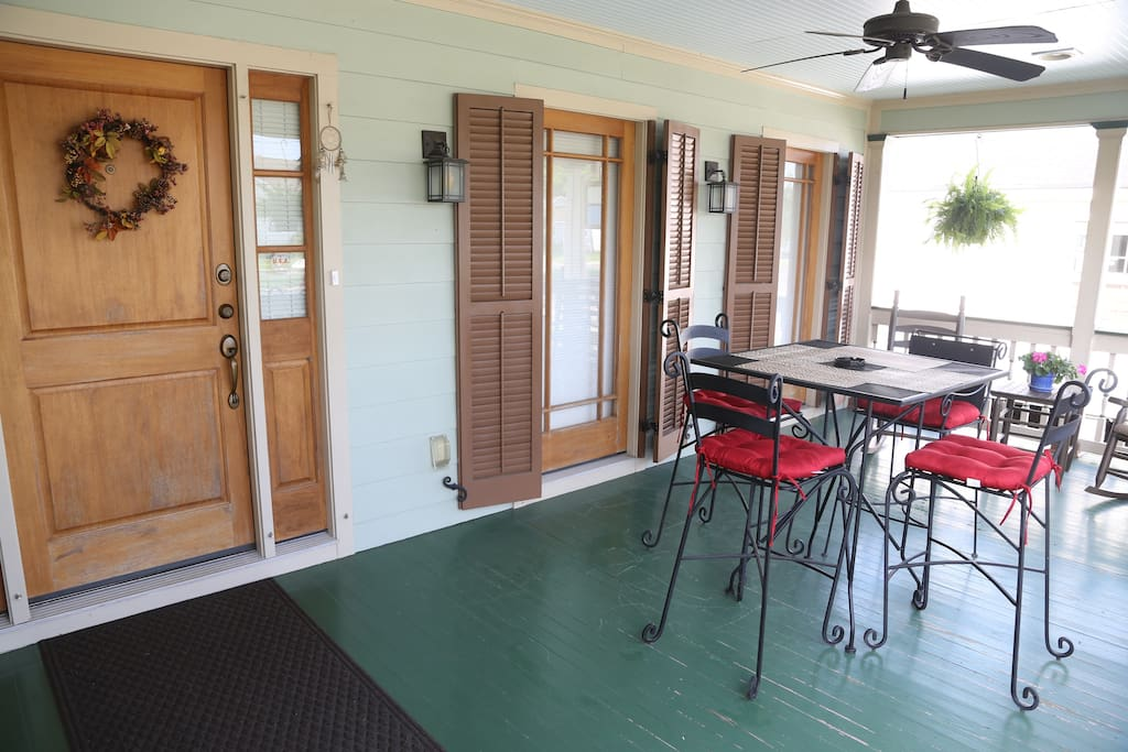 Large front porch with dining table and 2 rocking chairs