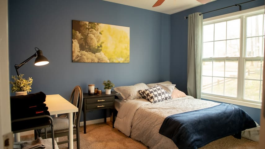 Bedroom 1: Located on the upper floor, this room features one full-sized bed, one nightstand with a usb charging station, and a writing desk with task lighting. A spacious room for one or a cozy couple!
