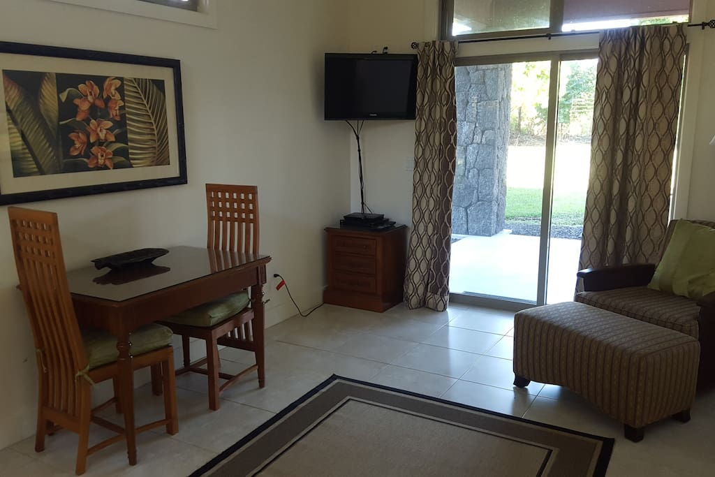 Living room area with sitting area, dining table, TV and direct access to covered patio.