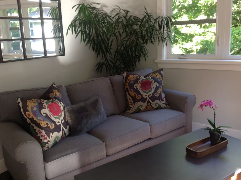 Cozy bright living room with lots of windows for beautiful treetop and garden views.