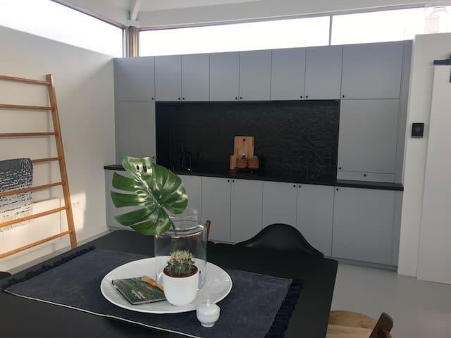 Open keuken voorzien van o.a. koelkast, 4-pits kookplaat, oven en afzuigkap. Thee en koffie is van het huis!