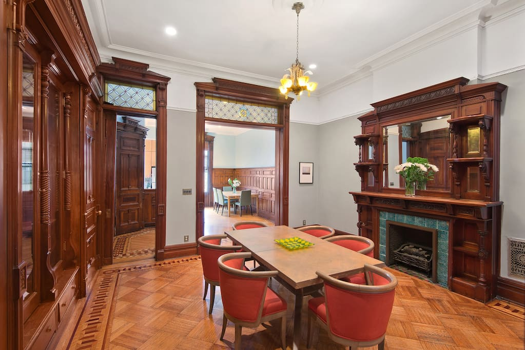 The all original parlors and the formal dining room include many stained glass panels, 10 foot tall fireplace mantles, built-in floor to ceiling china cabinetry, elaborate flooring and oak panel wainscoting.
