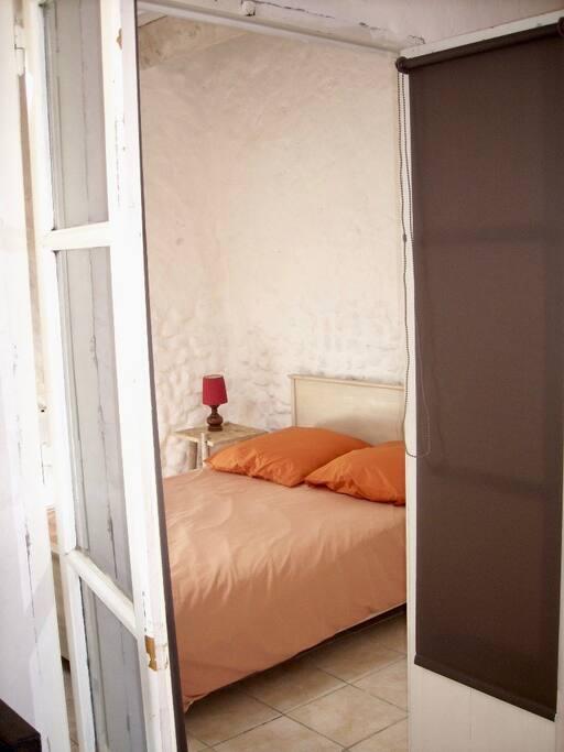 Chambre avec penderie et étagères.