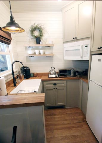 Kitchen with refrigerator and freezer, Keurig, microwave and toaster oven,  hot plates, slow cooker, NutriBullet, electric skillet, tableware, cookware, and kitchenware.