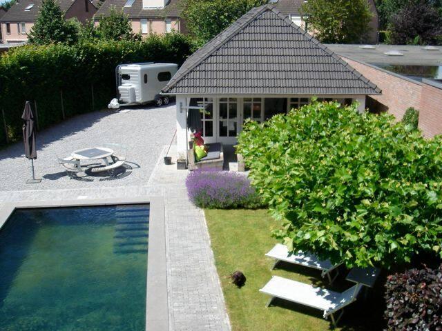Zicht vanaf boven op gastenverblijf, tuin en zwemvijver.