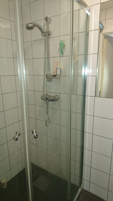The baderom with shower and tiled floor and walls