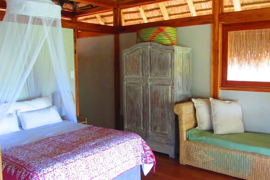 Ensuit bedroom with ceiling fan and upgraded 4 poster bed with wrap around mozzarella net - inland views from the bed