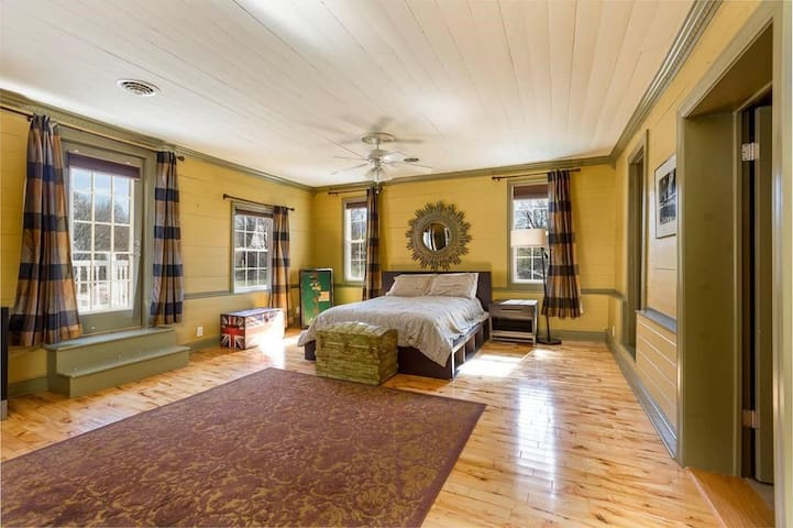 This contemporary bedroom with queen mattress is one of the largest rooms in the house and has balcony access. It also has a loveseat, a walk-in closet, furniture for storage, two small recliners, a flatscreen TV with Amazon Fire Stick, and a desk.