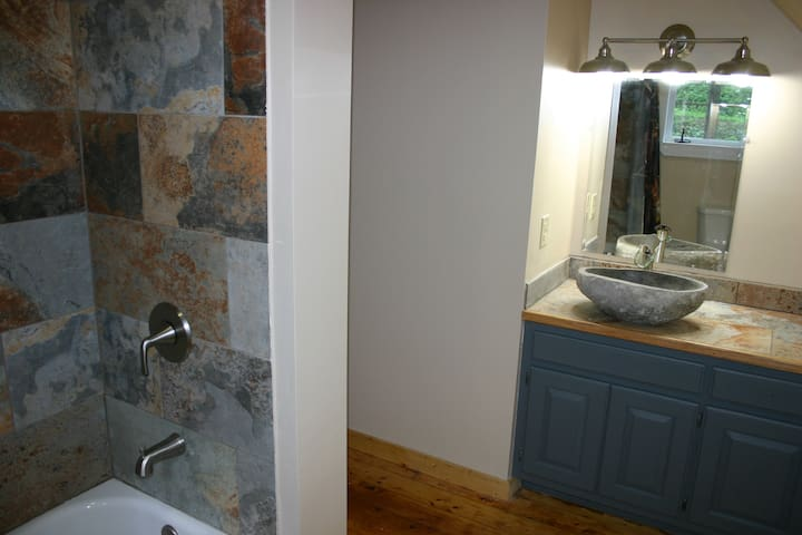 Guest bath with stone sink and tile shower/ bathtub