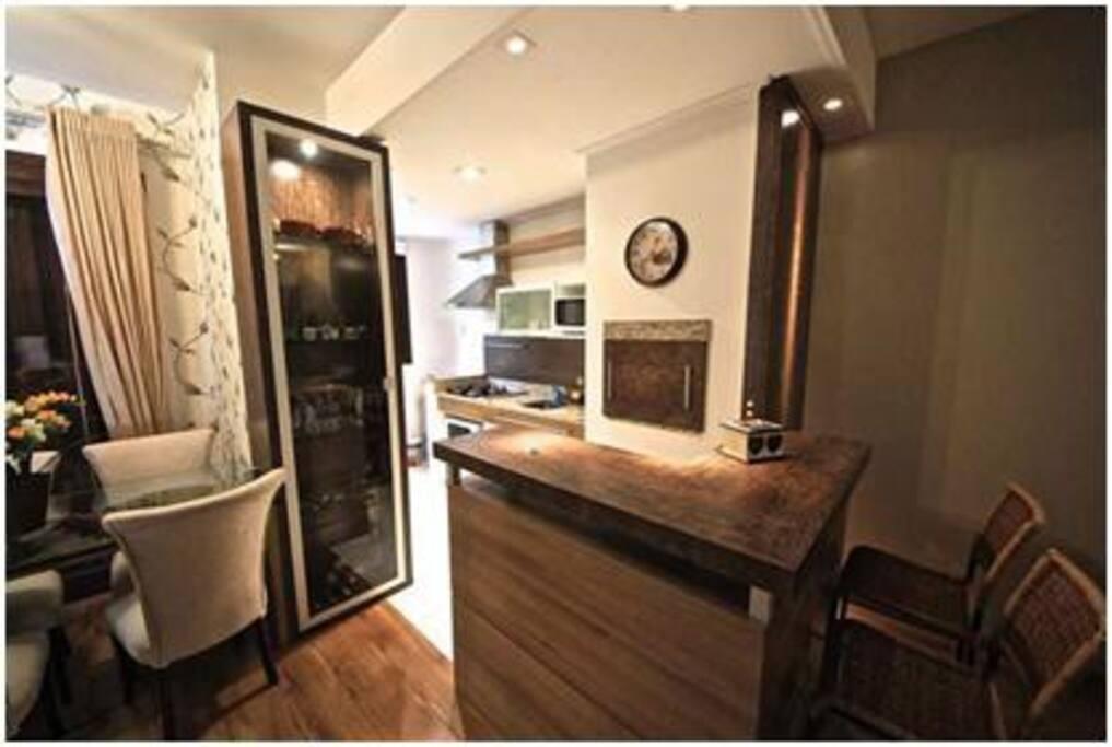 A sala é integrada à cozinha americana, com churrasqueira.