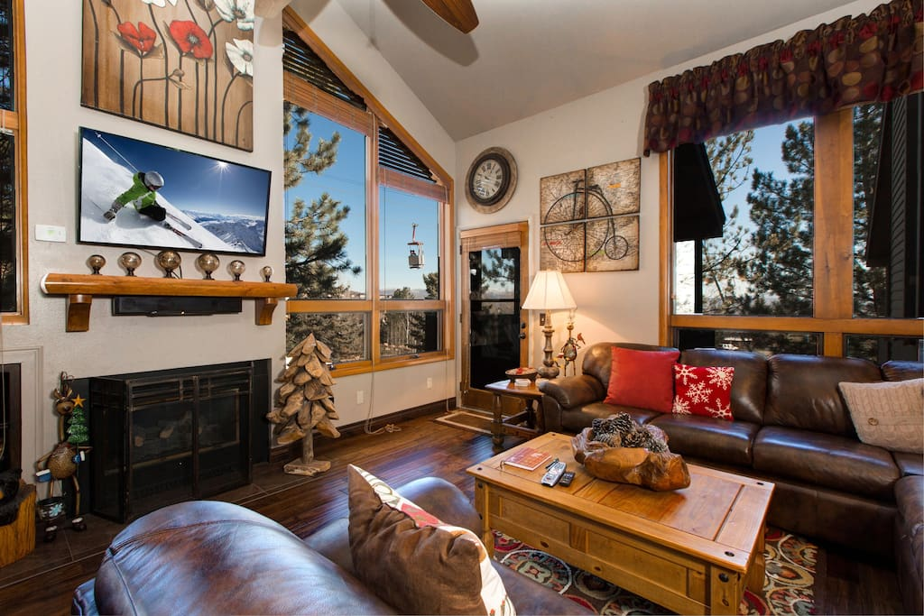 Cozy and classic living area with a flat-screen TV and wooded views through large windows.