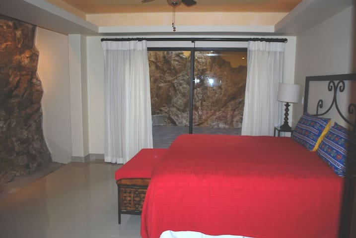 Upstairs bedroom with natural rock wall. Private patio with waterfall.