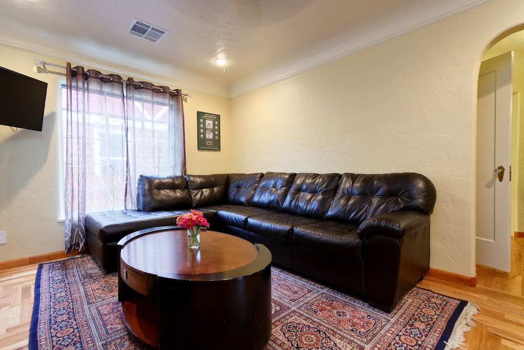 Open floor plan with comfy living room, Roku with movie channels and TV. Refinished hardwood floors throughout and original 1930s coved ceilings.