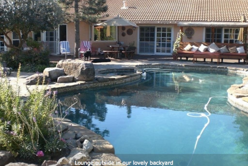 Large back yard with pool, hot tub, bocce court & grill.