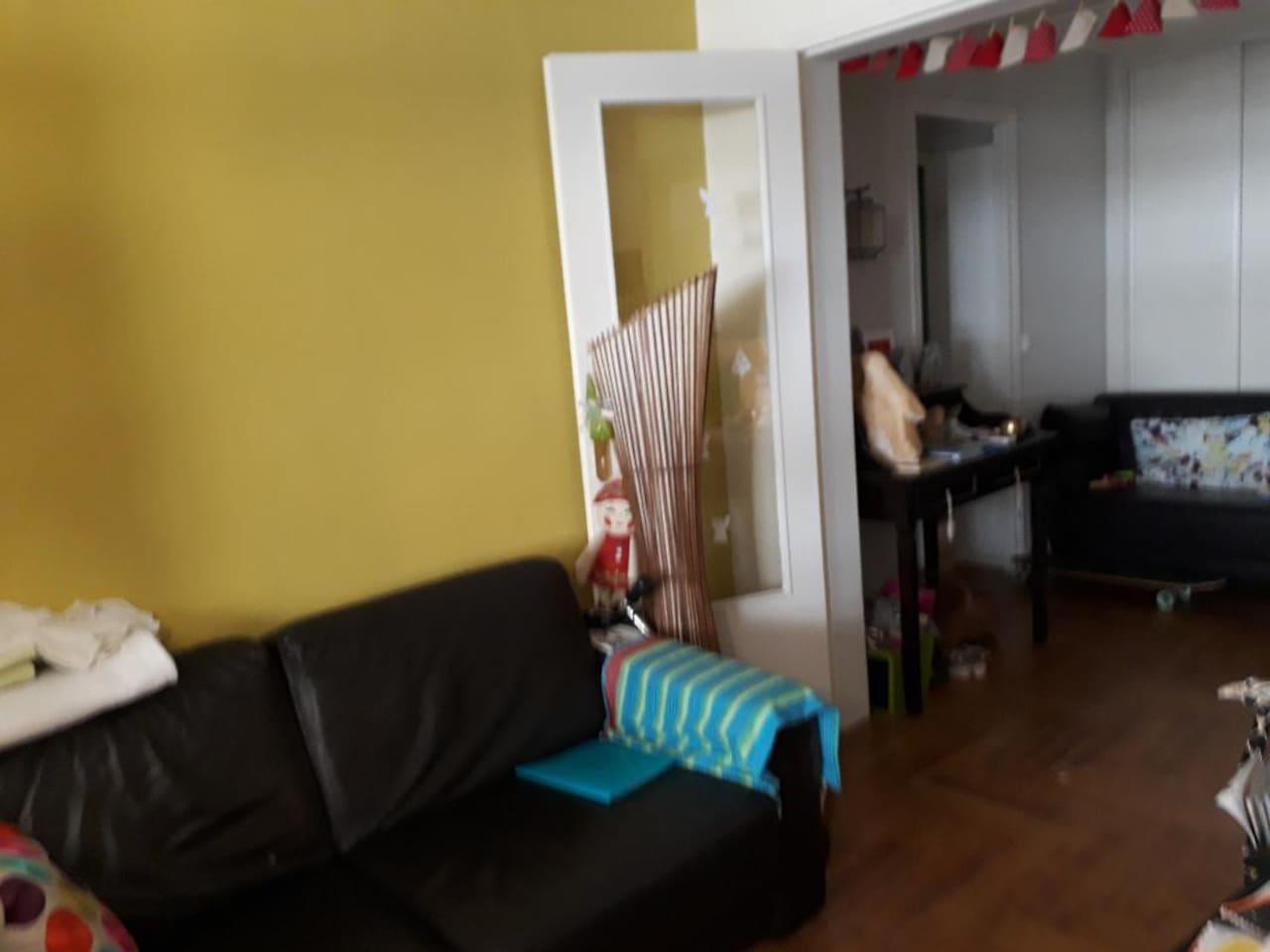A droite, entrée de l'appartement avec canapé sur la droite.
