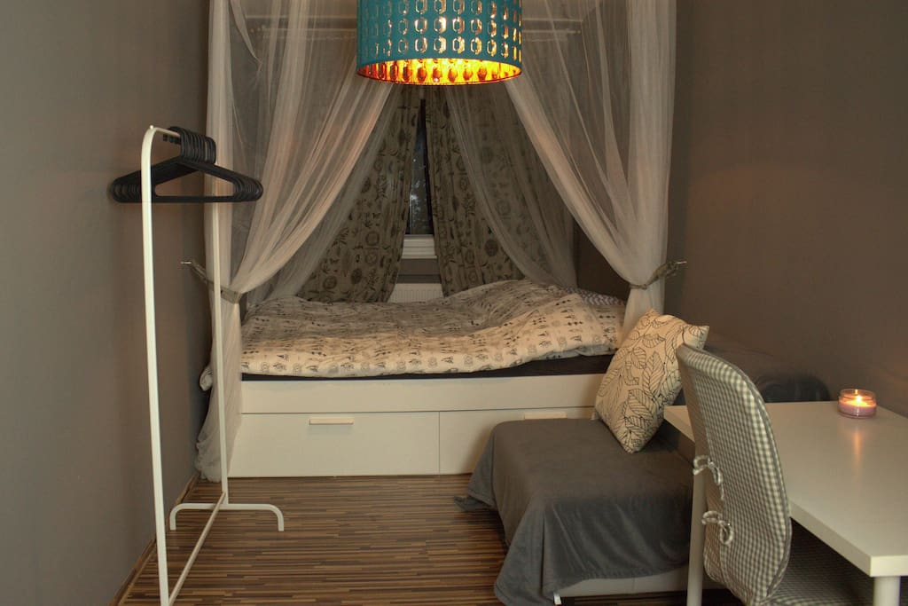 Das Gästezimmer mit Kleiderstange, Arbeitsplatz, Sitzgelegenheit, kleinem Regal (links, nicht im Bild) und Doppelbett.
