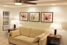 Living Room has couch, side tables and lamps, air conditioner, ceiling fan