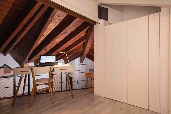 Particolare della scrivania del soppalco con porta scorrevole aperta ed affaccio nella zona giorno