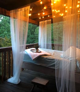 True log cabin with outdoor hanging full-sized bed