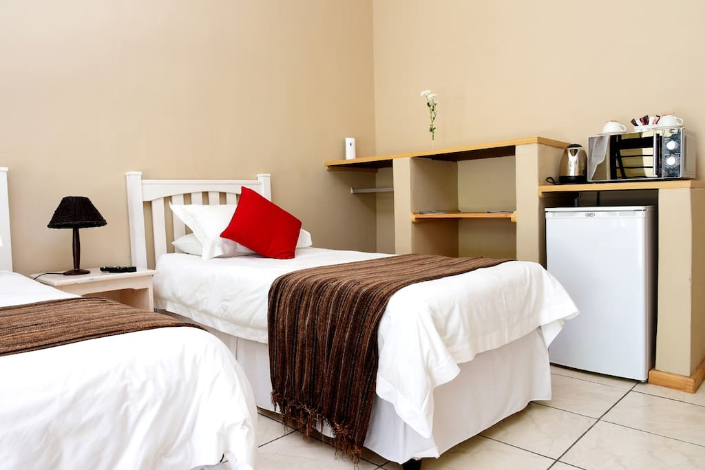 Room with fridge, microwave, crockery and kettle