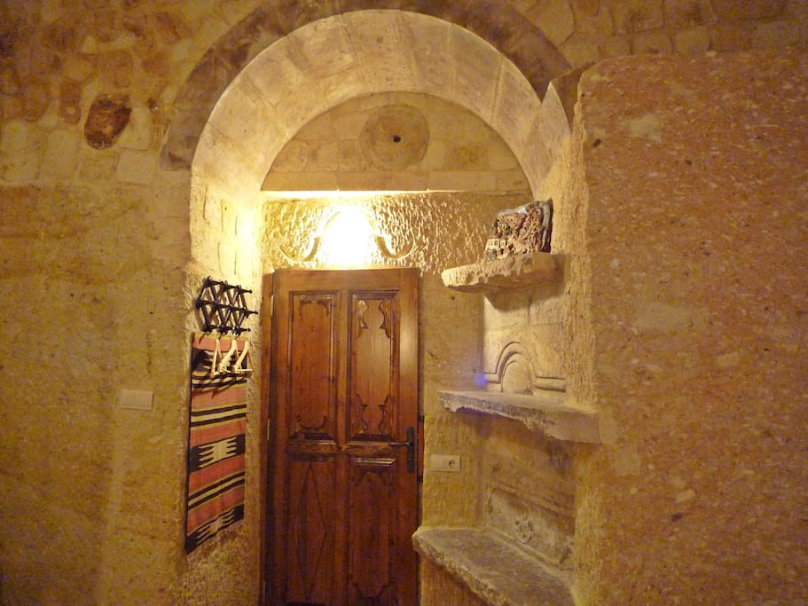Roman suite cave bedroom, traditional clothes hanging space, door to bathroom.
