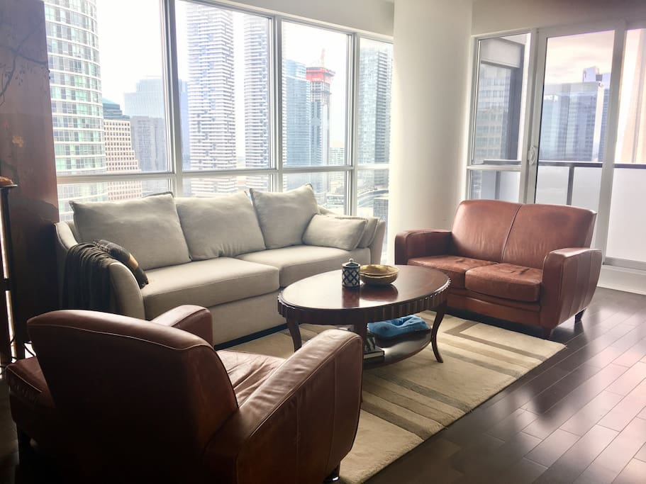 Enjoy spectacular views of  CN tower and lakeshore sitting on sofa