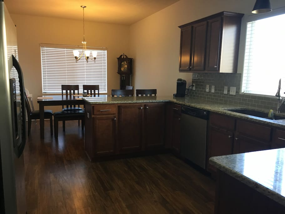 Bright and cheerful kitchen with eating area. Electric stove and oven. Dishwasher and refrigerator. Granite counters.