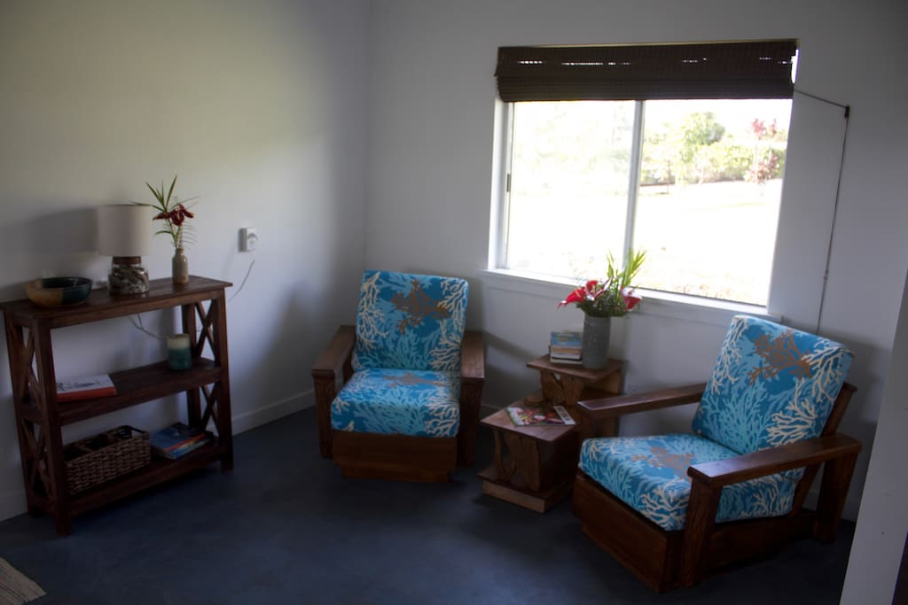 Sitting area, with refinished antique Hawaiian Koa wood chairs and table, stained concrete floors.