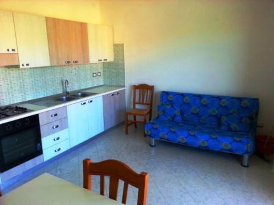 soggiorno con divano letto matrimoniale e angolo cottura