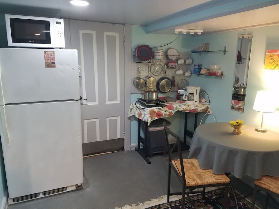 Kitchenette with full size refrigerator, toaster, coffee maker, microwave, and one burner.
