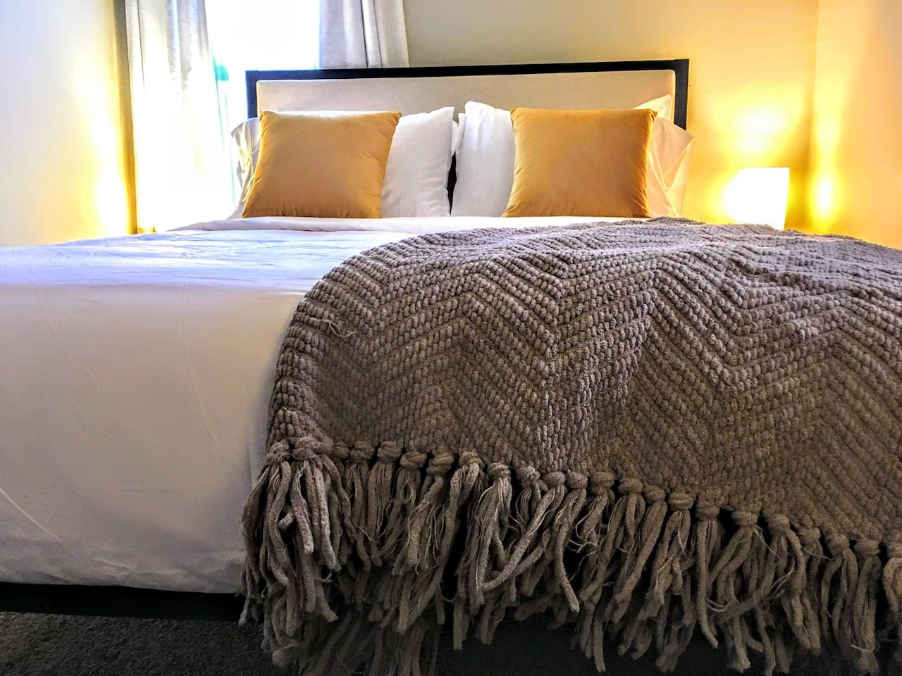 Cozy and chic Queen sized bed in the master bedroom of the flat, with a bedside table on either side; featuring a reading lamps that includes a built-in outlet on the lamp for easy phone charging.