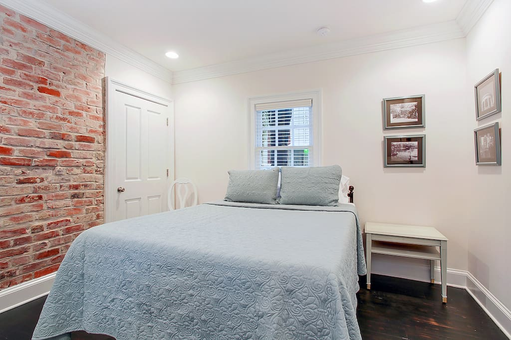 Master bedroom has exposed brick and closet.