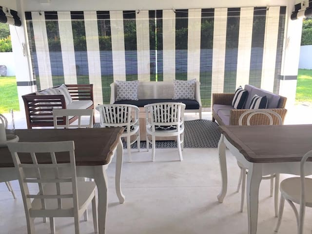 Verandah with dining for 12 and an outdoor seating area.