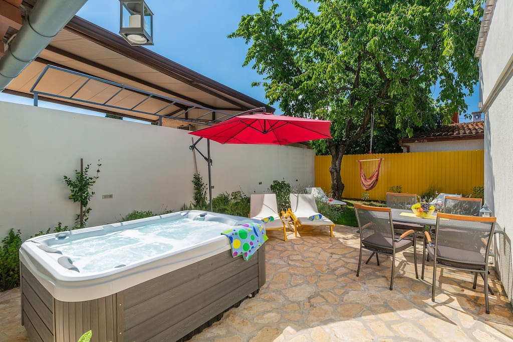 Private terrace with outdoor hot tub and garden furniture, surrounded by aromatic greenery