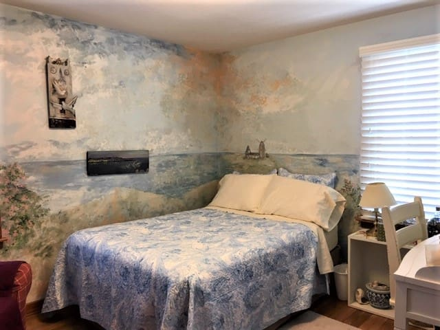 The double bed may have a variety of different coverlets that change up the decor but the wall mural creates serenity!