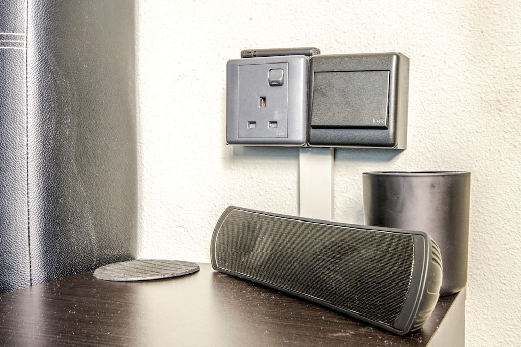 Bluetooth speaker, scented candle atop bedside table