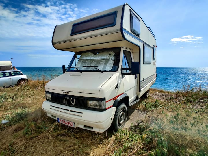 Vintage camper on the beach, off the grid