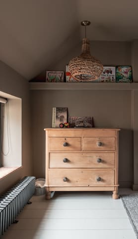 The twin bedroom, with painted floorboards, vintage chest of drawers, and plenty of childrens' books to enjoy!