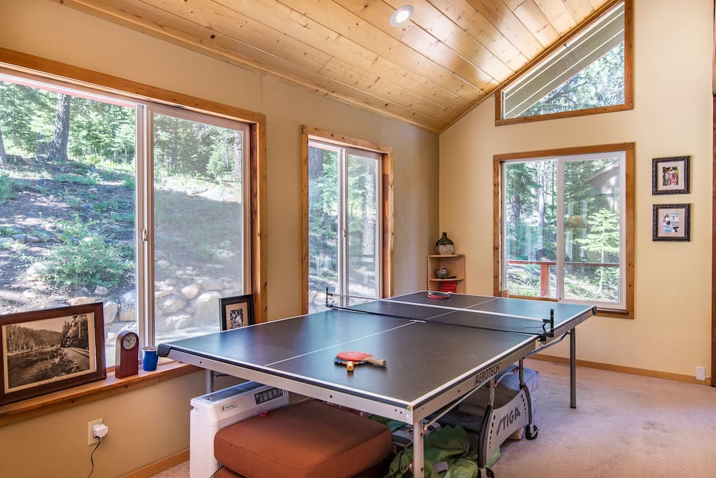 Enjoy a friendly game of ping-pong in the well-lit living room.