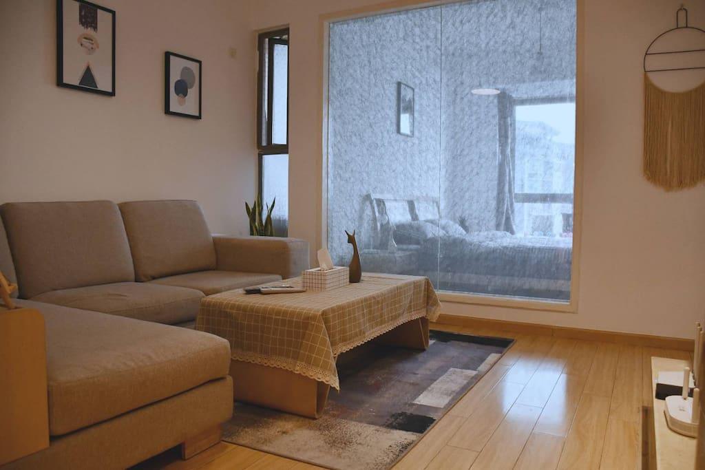 原木亮色挂画装饰的沙发背景墙,配合布艺沙发,使得整个客厅既时尚又舒适。