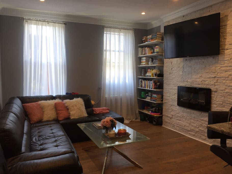 High end and cozy living room area with views of Washington Street, an electric fireplace, central heat, small library and TV.