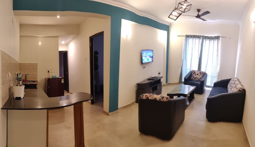 Living area has a beautiful view with balcony , it's a big room with 5 seater sofa and beautiful b open kitchenette with all basic amenities for Indian cooking .