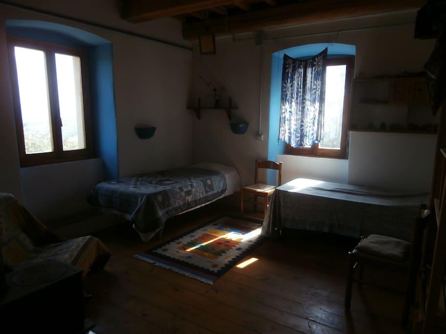 Stanza blu con due letti singoli ed accesso alla stanza gioco/studio